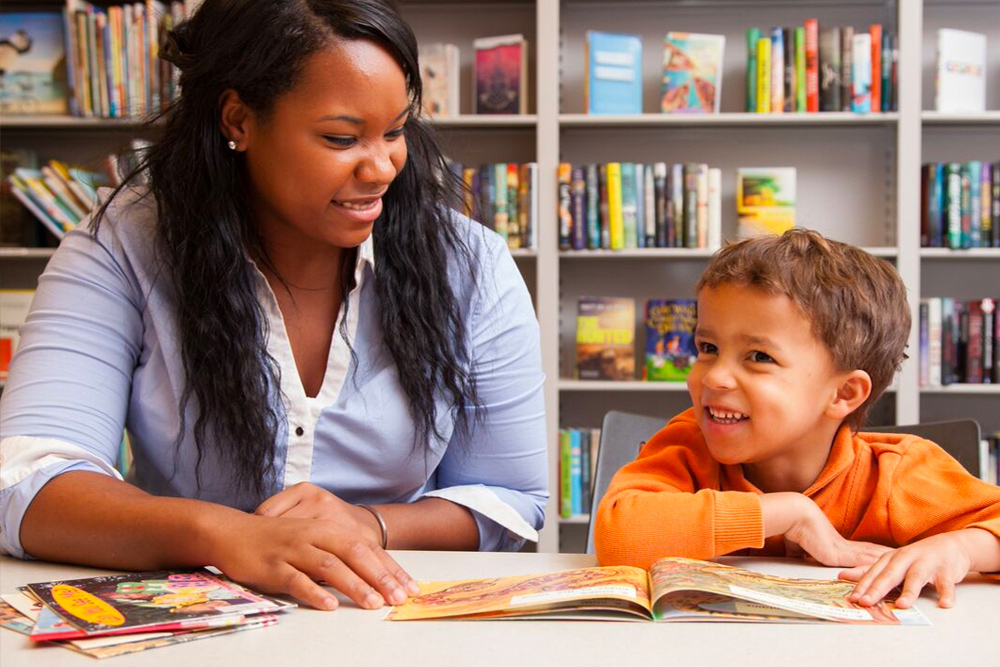 Student teacher reads book with a student