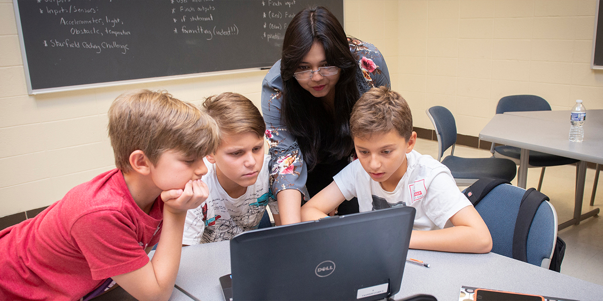 Teacher points to laptop screen as she helps three students with an assignment