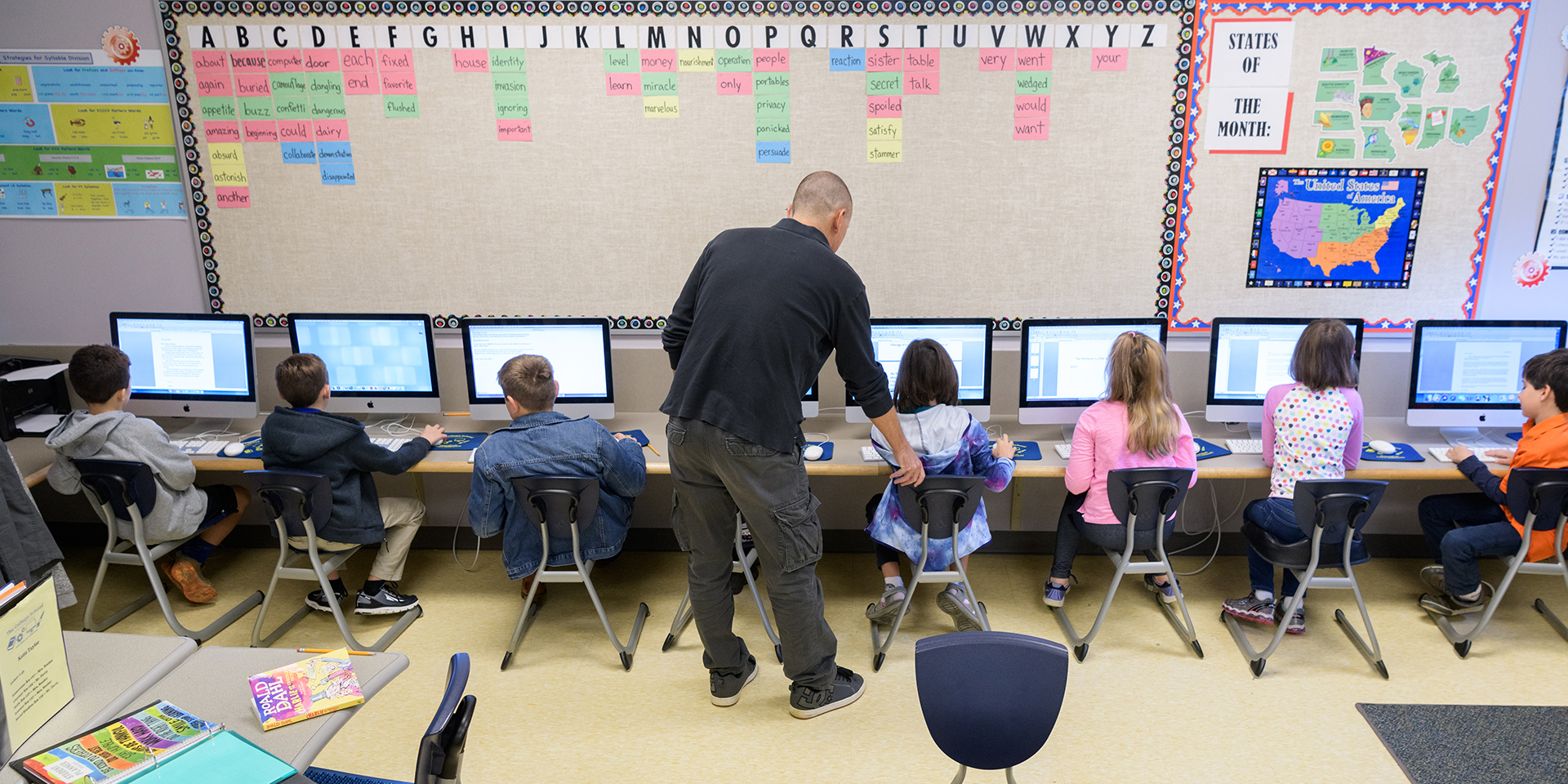 Teacher shows young students how to use computer program