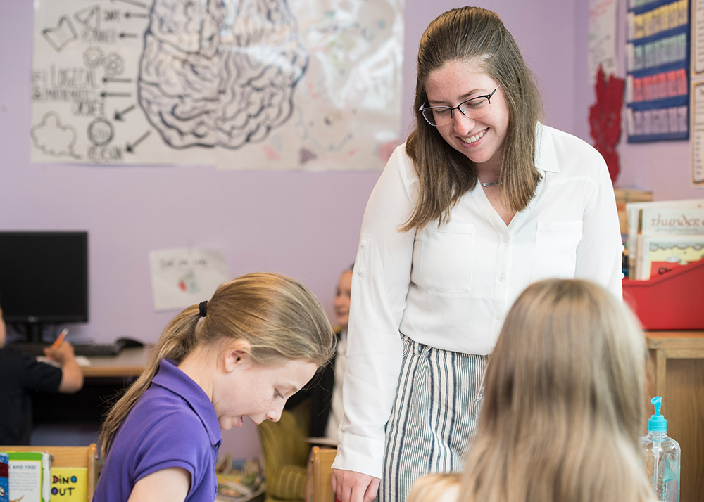 Student teacher smiles at two students in a classroom
