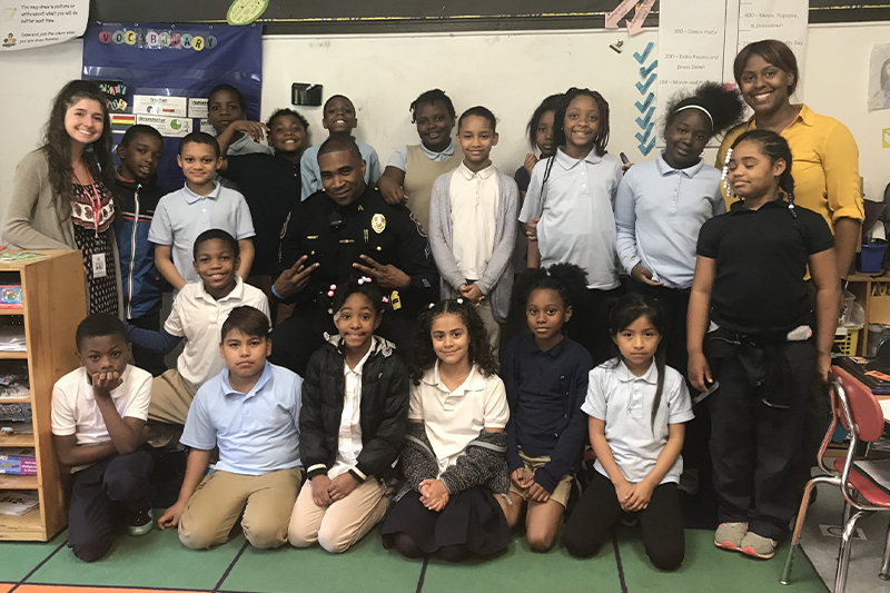 An elementary class at Warner Elementary poses for a group photo with a community police officer